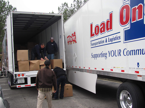 Load One trucks and people unloading them.