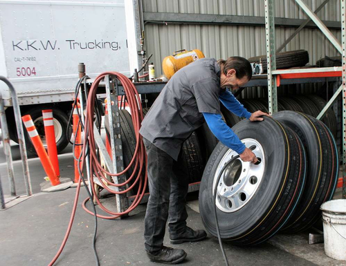 A technician for Pomona, Calif.-based KKW Trucking fills a truck tire with air. Proper inflation is critical for tires to enjoy a longer life.