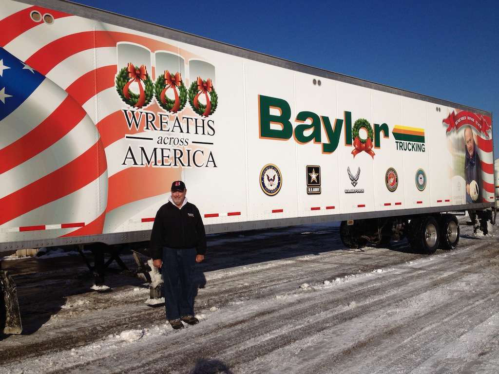 Baylor Trucking, Inc. President, Robert Baylor stands by the trailer which was used to deliver to several military cemeteries. This is the sixth straight year Indiana's Baylor Trucking has partnered with Wreaths Across America.