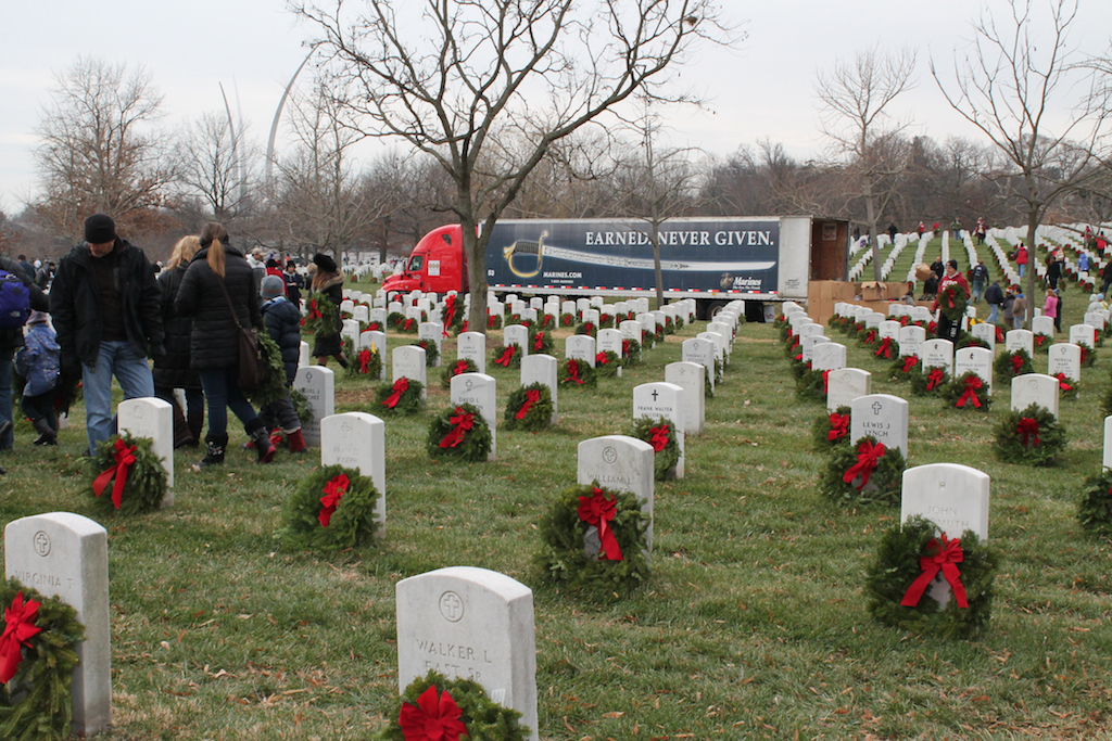 Volunteers place wreaths that were delivered by Bay & Bay Transportation, who decorated their trailer to honor the United States Marine Corps.