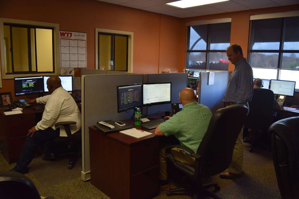 WTI's dispatch wing is equipped with about 8 dispatch stations, each of them anchored with two big monitors for dispatchers to work with. The window on the back wall in this picture is where drivers can come talk to the dispatchers.