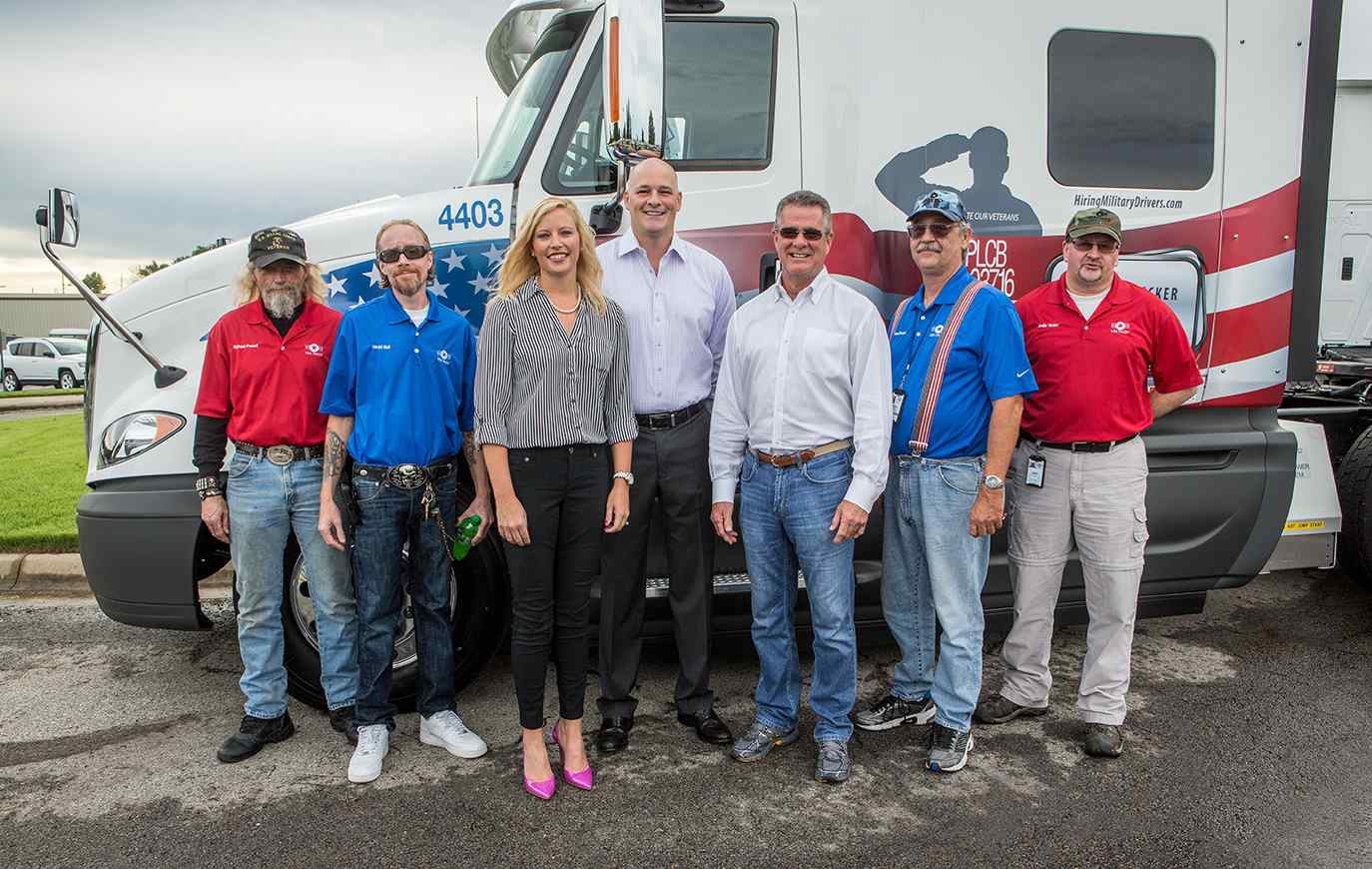 USA Truck presented four of its outstanding military veteran driving team members with personalized, military-themed tractors during a celebration September 11, 2015 at the Company's corporate headquarters in Van Buren, AR. Pictured from left: Michael Powell, U.S. Marines veteran; David Bell, U.S. Navy veteran; Shannon Newton, President of the Arkansas Trucking Association; Russell Overla, Executive Vice President of Truckload Operations for USA Truck; Tom Glaser, President & CEO of USA Truck; Robert Decker, U.S. Air Force veteran; and Jodie Yoder, U.S. Army veteran.