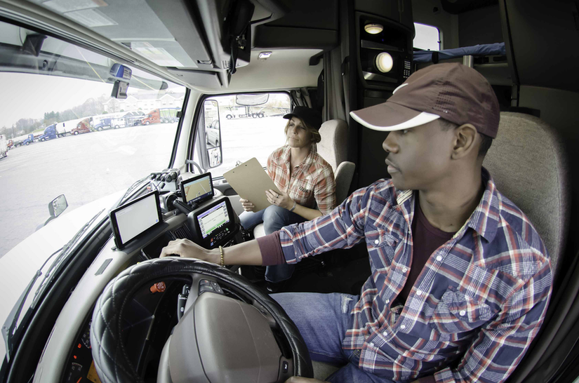 Truck driver with trainer in the cab of truck