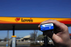 Person holding a Transflo device in front of a Love's Travel Stop location