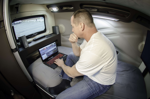Trucker on his laptop in the sleeper berth of his truck