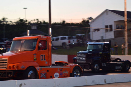 Two truck towing a Mack race truck