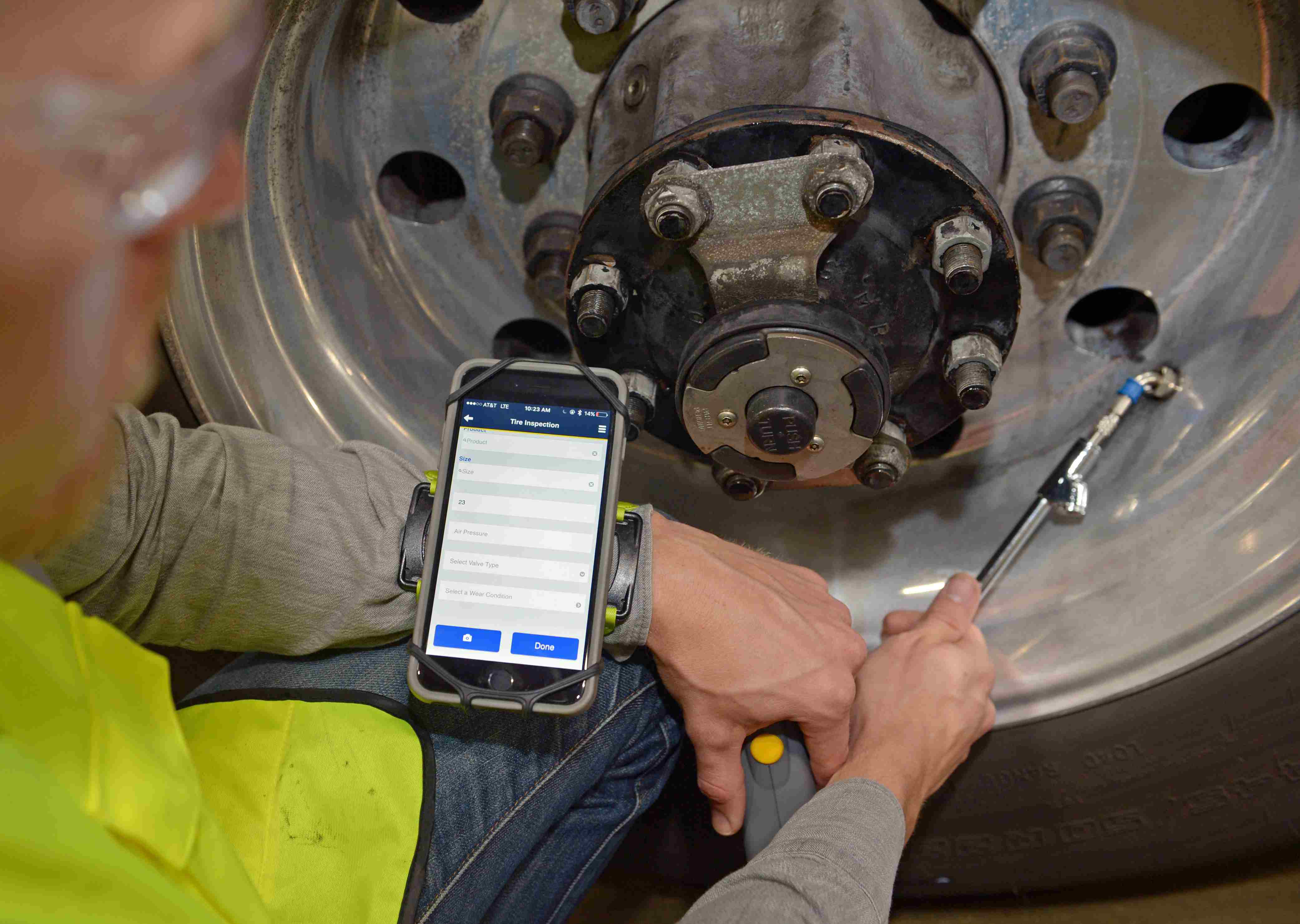 Technician using app while fixing tire