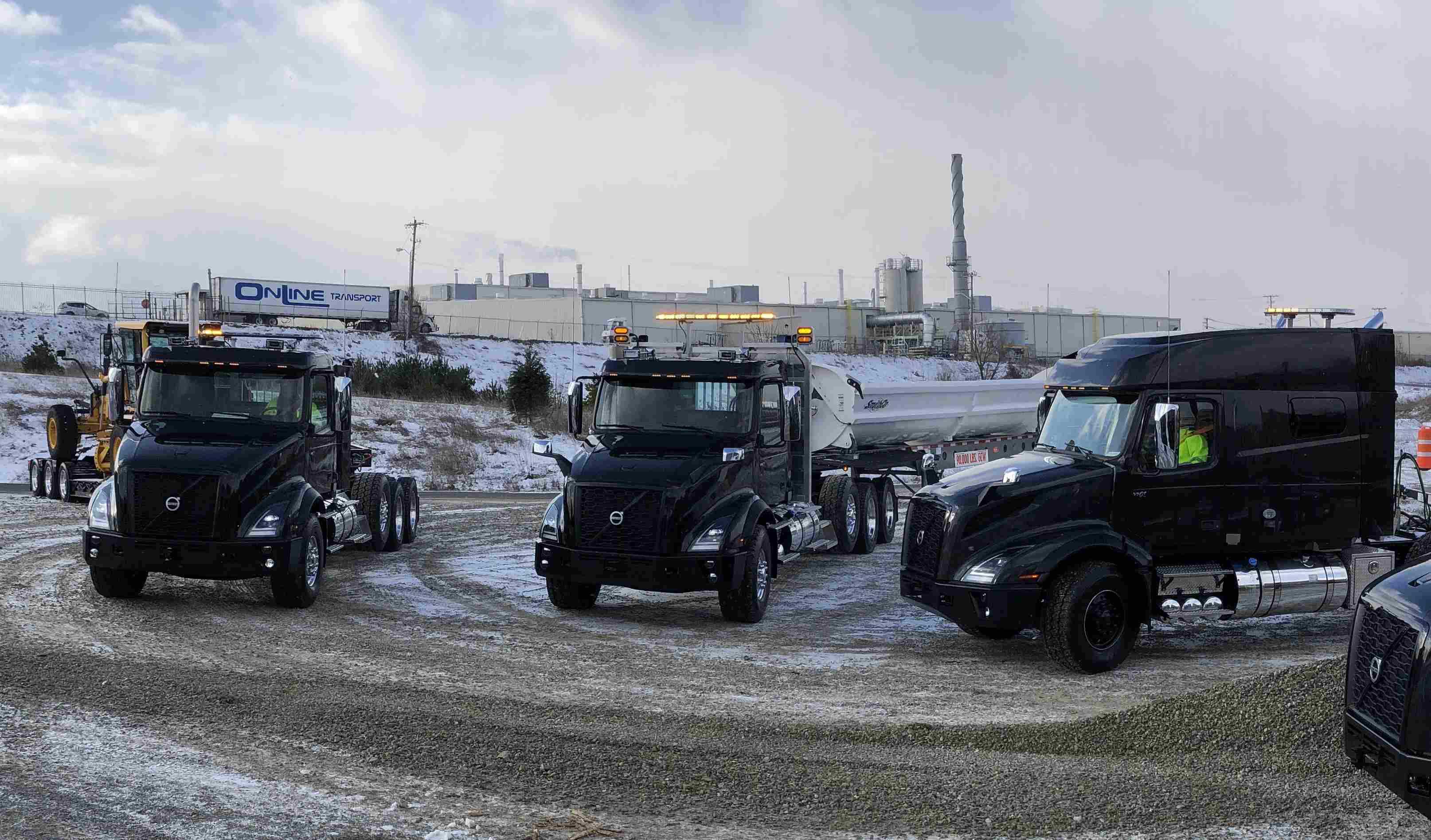 Three Volvo VNX series semi trucks parked