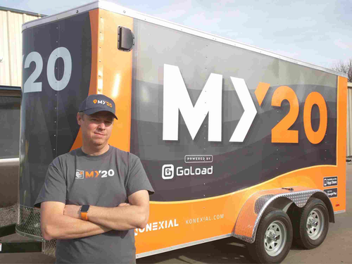 Person in front of Konexial's My20 app trailer