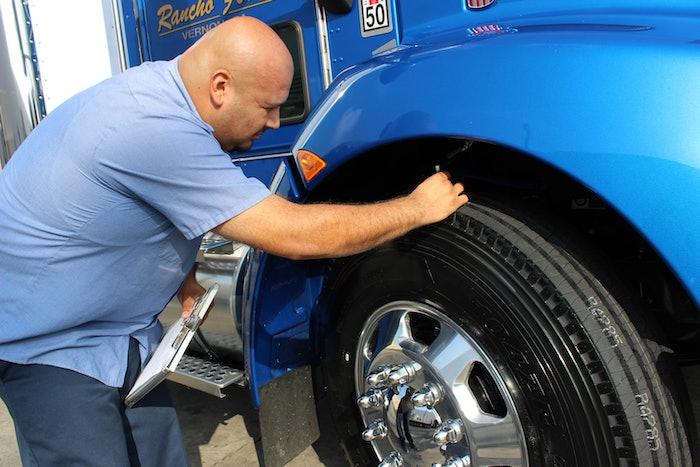 man checking tire tread depth