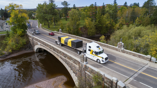 Halvor Lines flatbed truck crossing a bridge