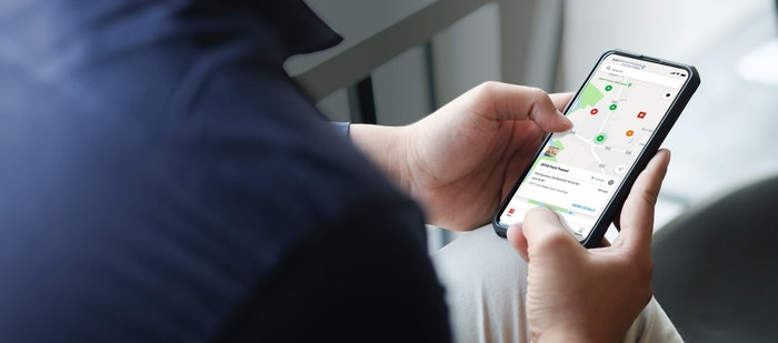 Cropped shot view of man hands holding smart phone with blank copy space screen for your text message or information content, female reading text message on cell telephone during in urban setting.
