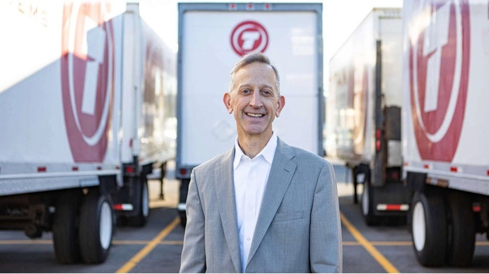 Keith Wilson, president of Titan Freight Systems, standing in front of Titan Freight semi-trucks