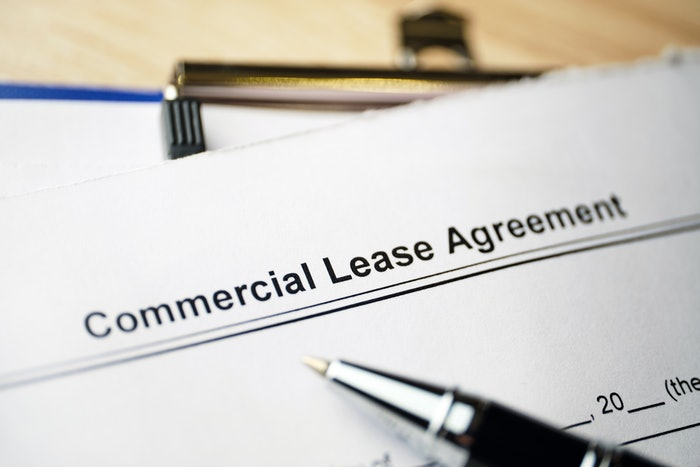 Commercial Lease Agreement form on a clipboard with a pen