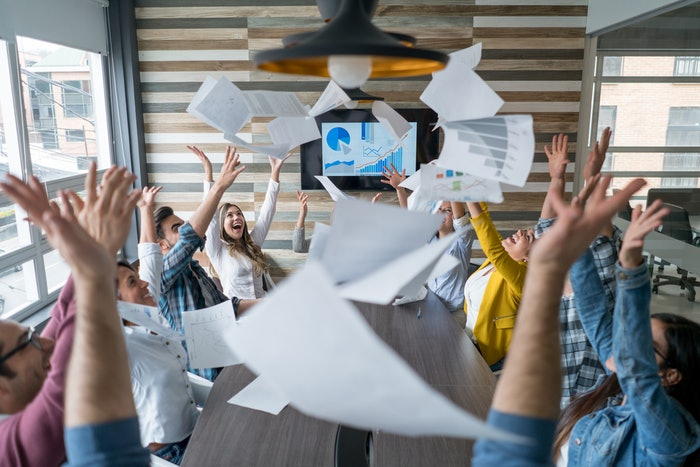 People sitting around desk throwing paper in the air