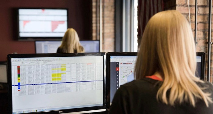 woman working desk with two monitors looking at data