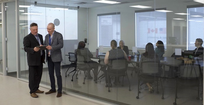 employees discussing technology in corporate setting
