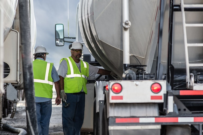 Two people in safety vests and hardhats standing between trucks in New Mexico