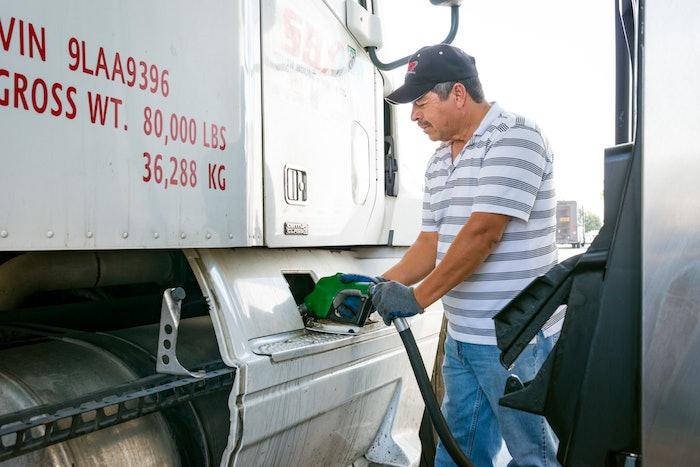 Man pumping fuel into a semi-truck