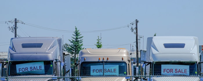 three white semi-trucks parked in a row with for sale signs in their front windows