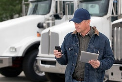 Man holding a tablet and checking his phone in front of parked semi-trucks