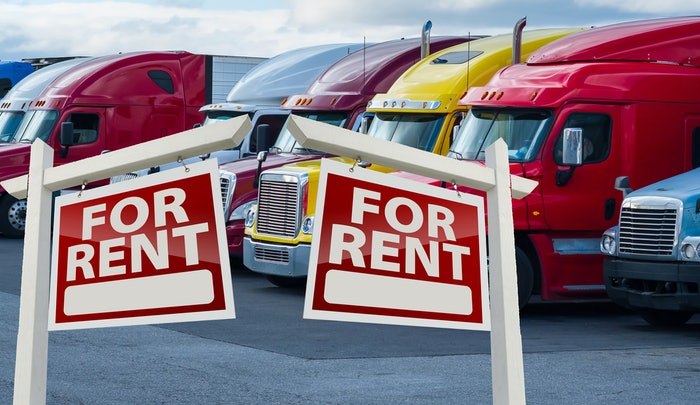 parked semi trucks with 'for rent' signs in front of them