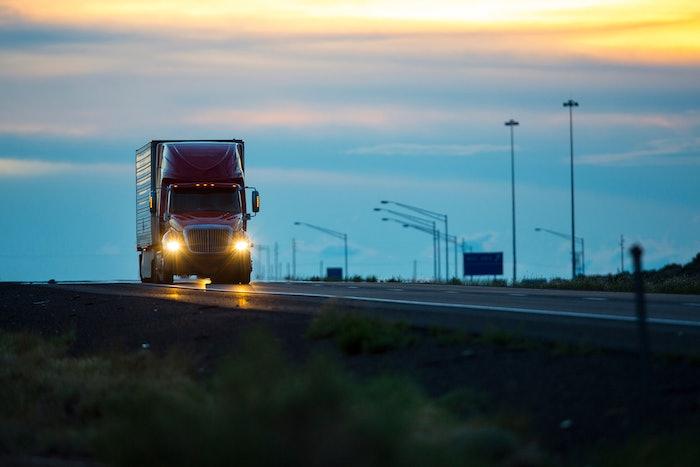 Semi-truck on empty highway at dusk