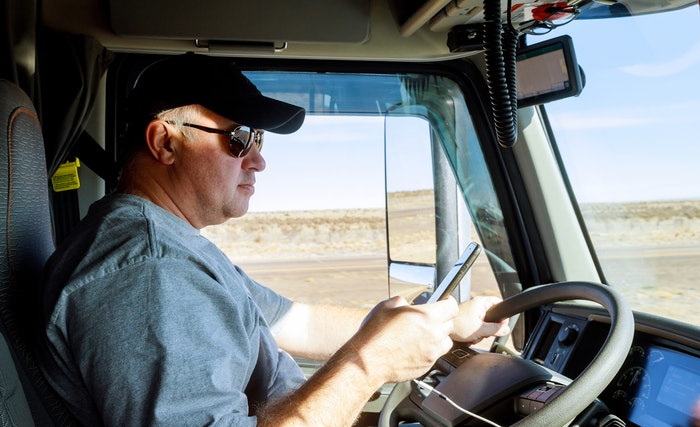 Truck driver behind the wheel looking at his phone