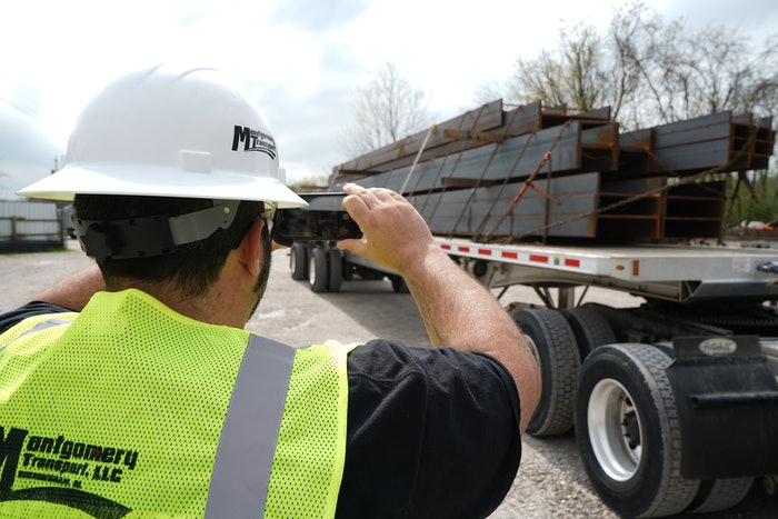 Montgomery Transport driver using his phone to take a picture of a load of steel beams