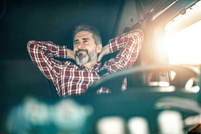 Man sitting in driver seat of truck