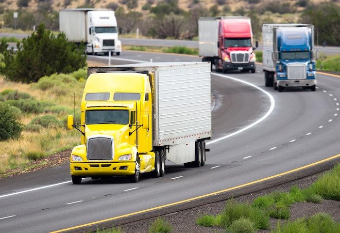 4 semi trucks on highway