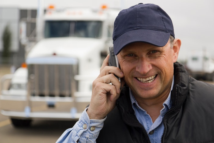 man on cellphone in front of semi truck