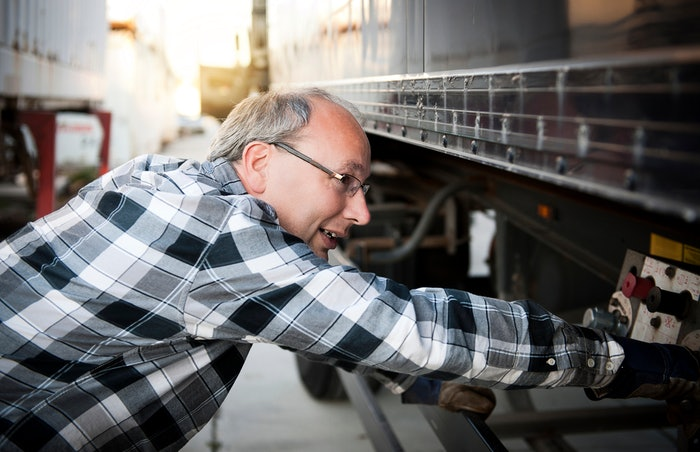 man performing truck maintenance inspection