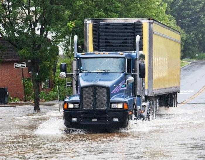 semi truck driving through flooded roadway