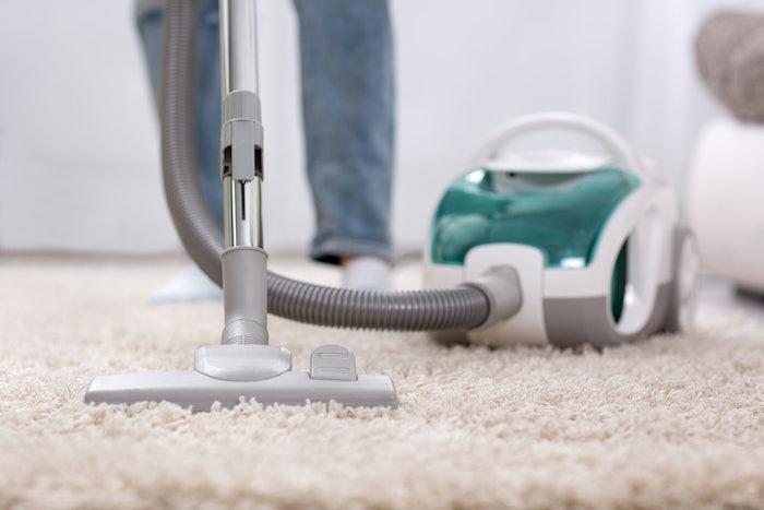 person using vacuum cleaner on carpet