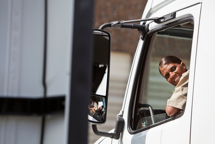 woman smiling out of drivers side window of truck