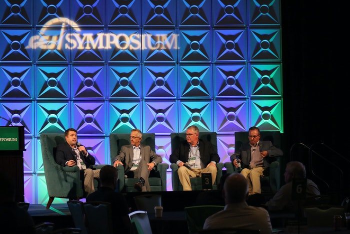 four men sitting in chairs on stage at the 2021 ccj symposium
