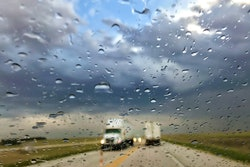 semi-trucks driving on a highway during a rainstorm